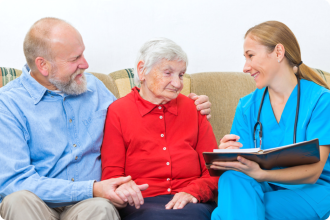 Two elderly listening to the caregiver
